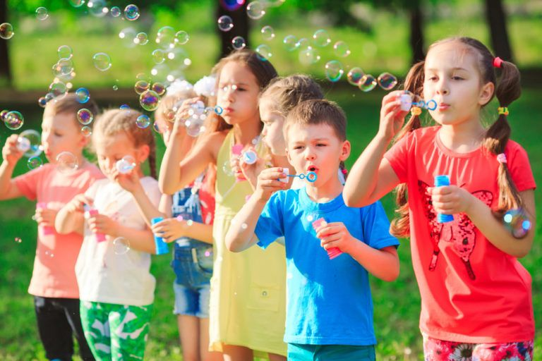 Group of children blowing soap bubbles